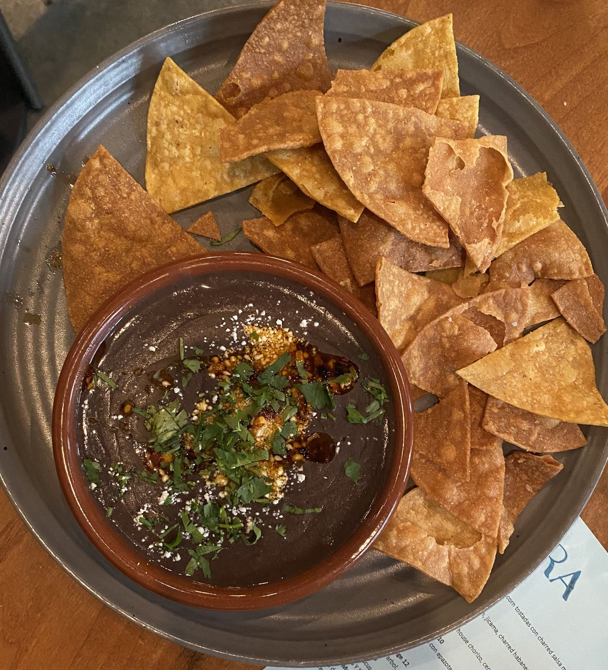 A bowl of black bean dip and thick chips on a grey plate.