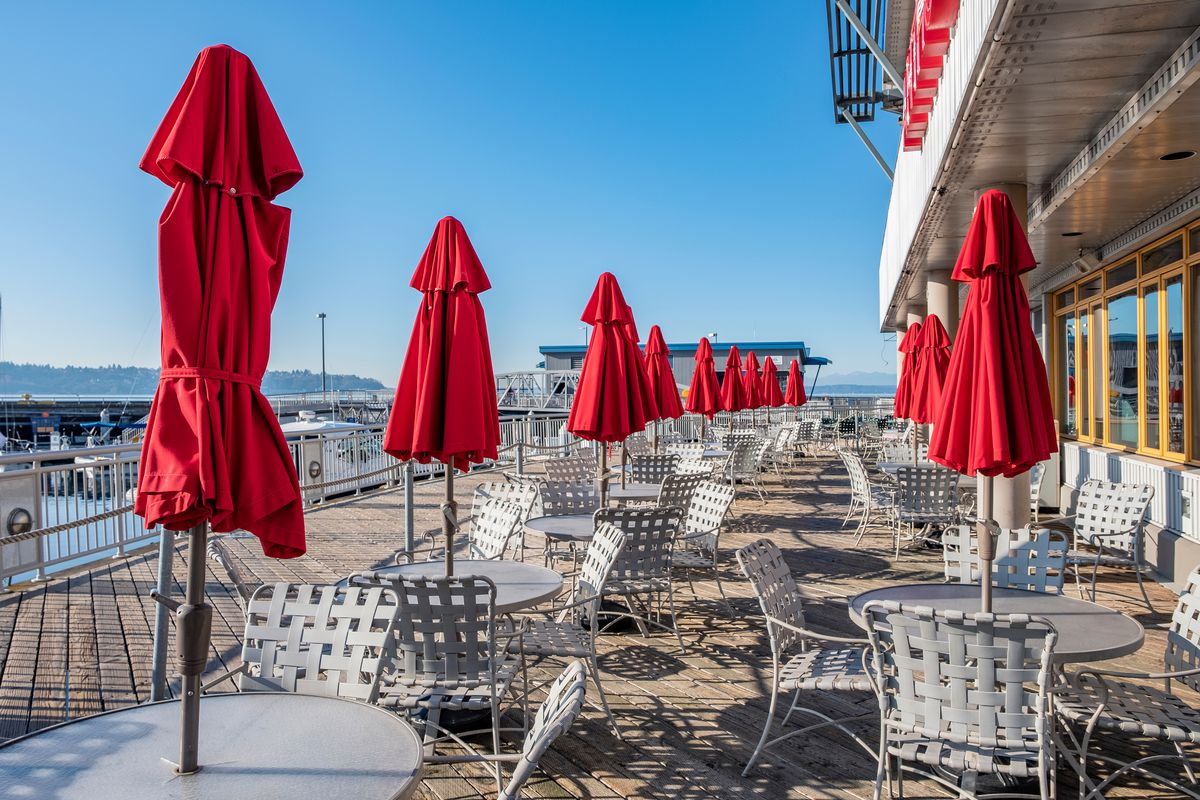 An outdoor restaurant patio overlooking the Puget Sound on a sunny day, with closed red umbrellas