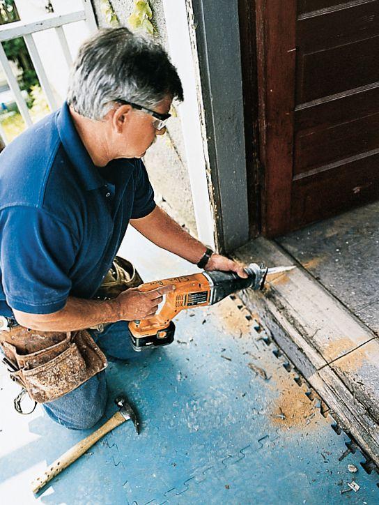 Man Using Wood-Cutting Blade To Slice Into Door Threshold