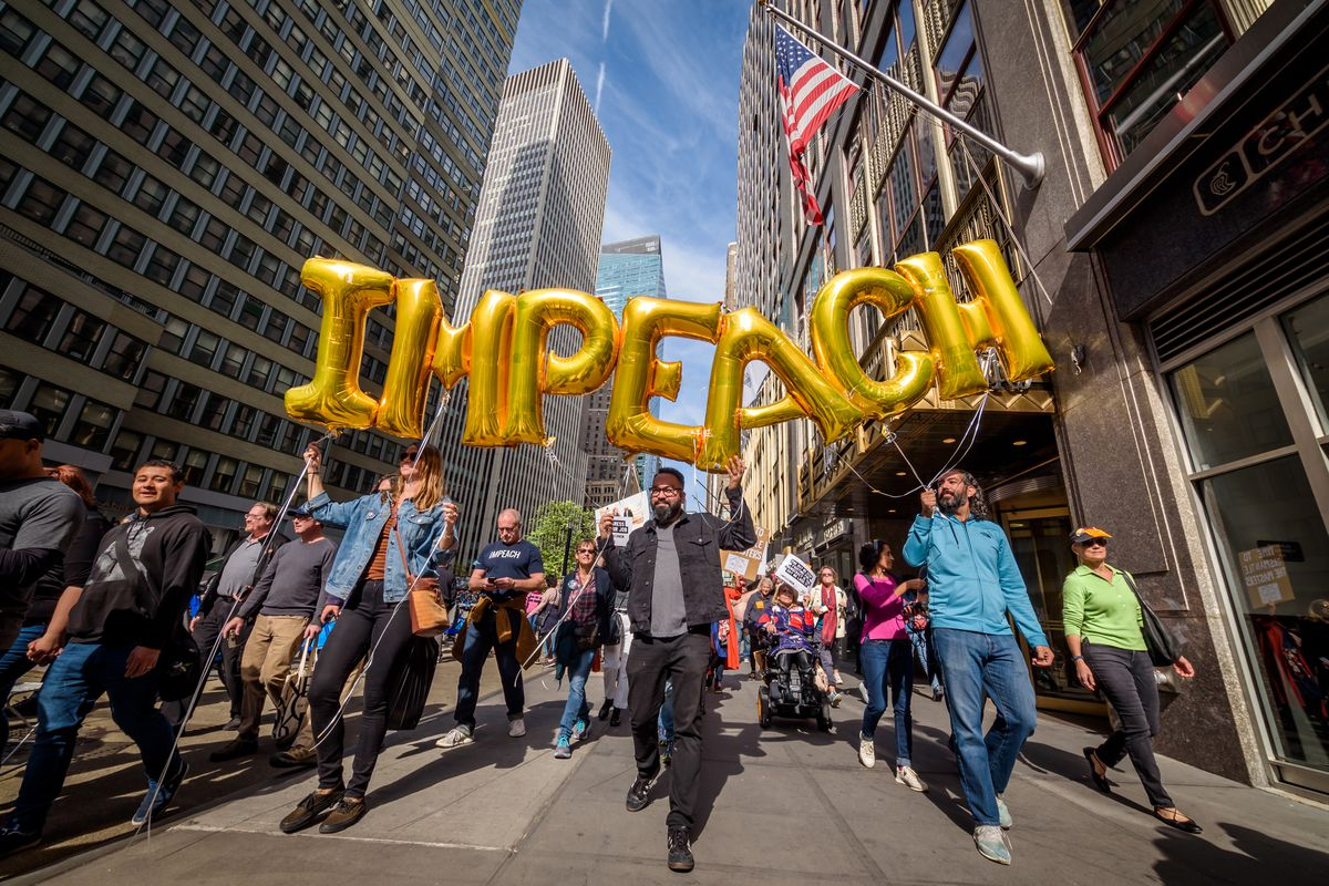 """Protesters carry gold foil letter balloons spelling out """"IMPEACH."""""""