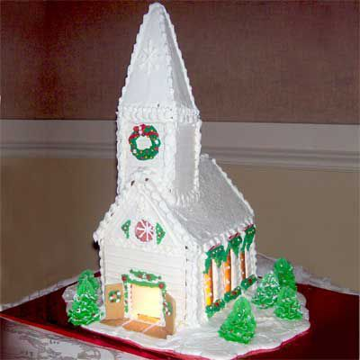 White gingerbread Chruch with green wreath made of icing.
