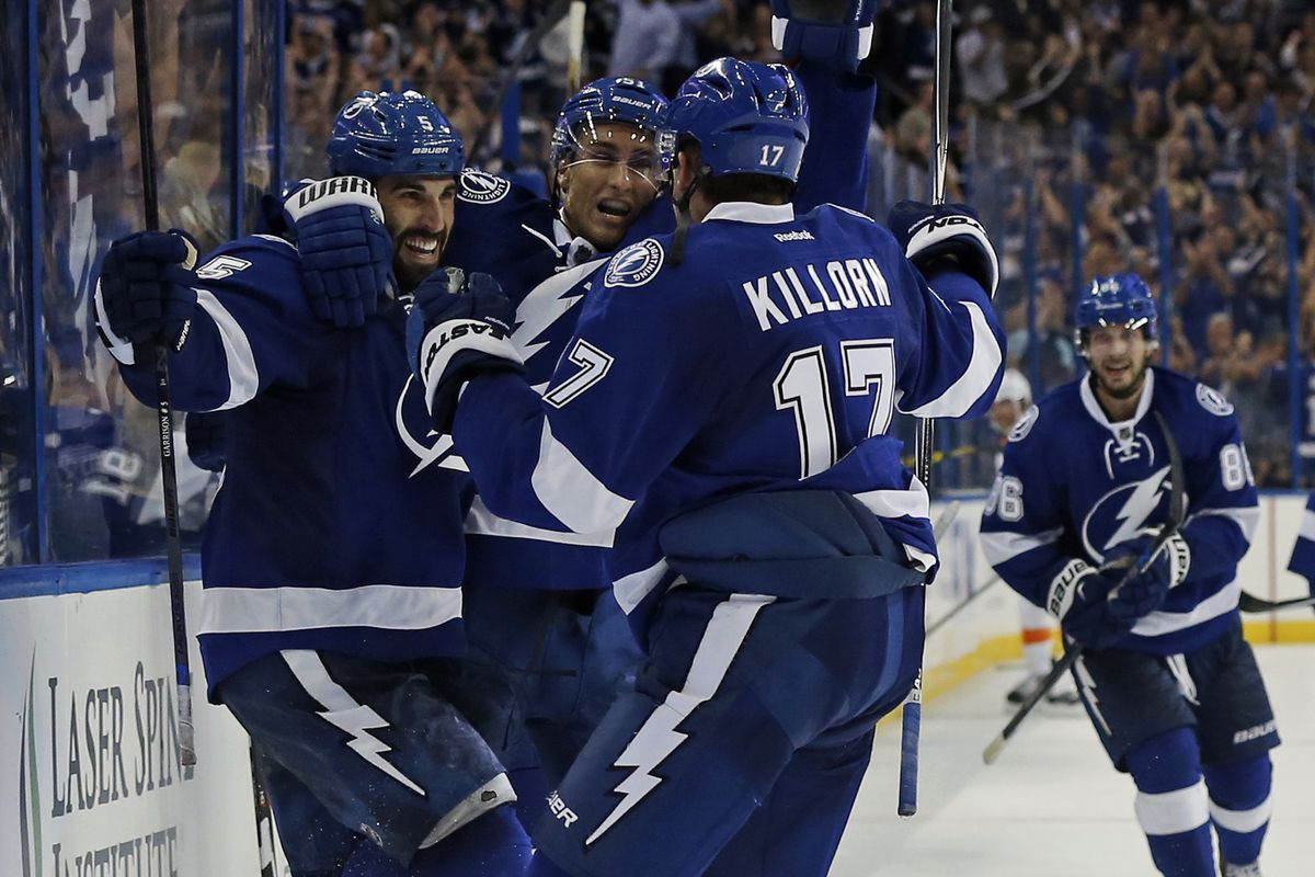 Jason Garrison #5 of the Tampa Bay Lightning (L) celebrates his overtime goal with teammates Valtteri Filppula #51 and Alex Killorn #17 against the Philadelphia Flyers at the Amalie Arena on October 8, 2015 in Tampa, Florida.