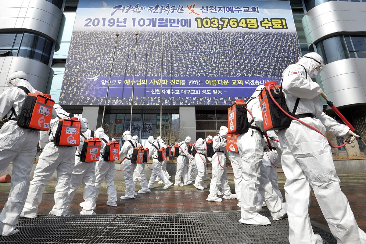 In this March 1, 2020, file photo, army soldiers wearing protective suits spray JJ disinfectant to prevent the spread of the coronavirus in front of a branch of the Shincheonji Church of Jesus in Daegu, South Korea. As the coronavirus spreads around the world, many events that normally would draw large numbers of people are being canceled or played without fans. (Lee Moo-ryul/Newsis via AP, File)