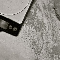 The scale, for precision weighing of each dough round.