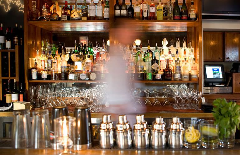 A blur of a bartender passes through the center of the frame, with a view of the restaurant's bar in the background, featuring several shelves of liquor, a variety of cocktail tools, and dark wood accents