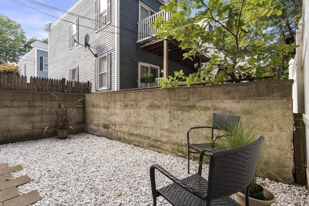 A gravel patio with chairs.