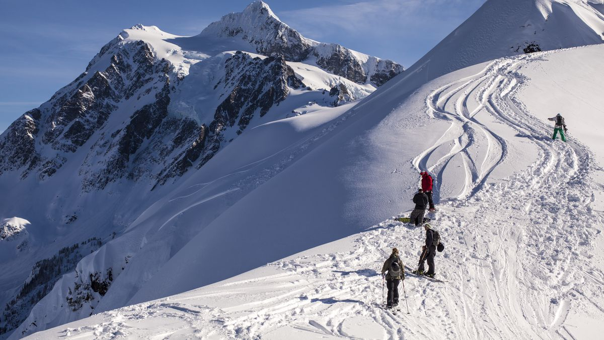 A snowy mountaintop. Two peaks are showing. The peak to the right is completely coated in snow, and has ski tracks running down from the top. Five skiers are at various positions along the tracks.