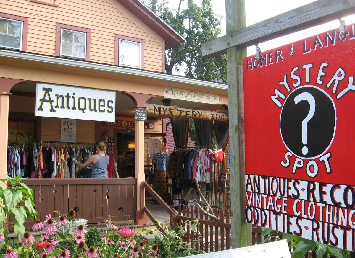 An antique shop. There is a sign hanging that reads Antiques. People are standing on the porch of the shop looking through items of clothing.