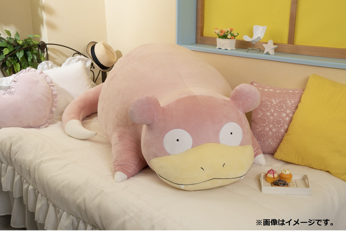 """Pokémon - a Slowpoke plush, measuring 47"""" inches across, vibes on a couch next to a plate of pastries for scale."""