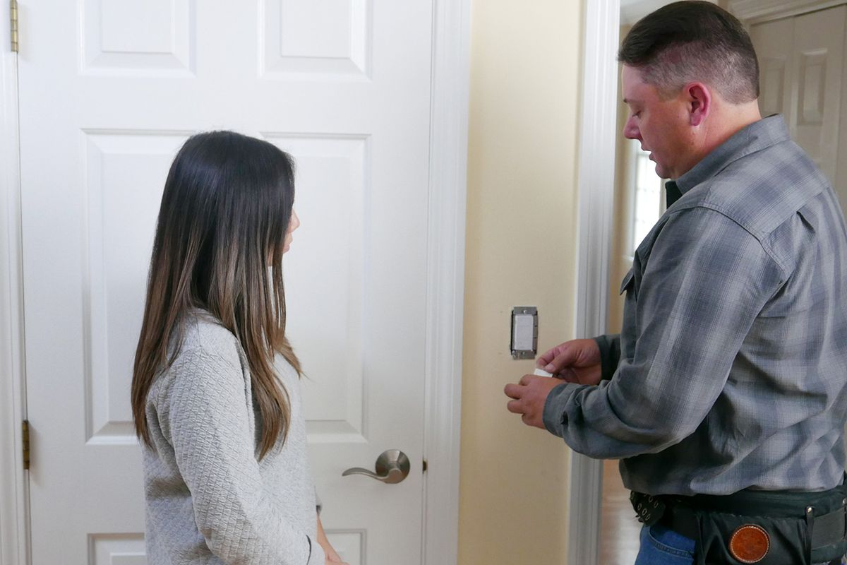 Electrician Heath Eastman shows a homeowner how to wirelessly connect more than one light switch.