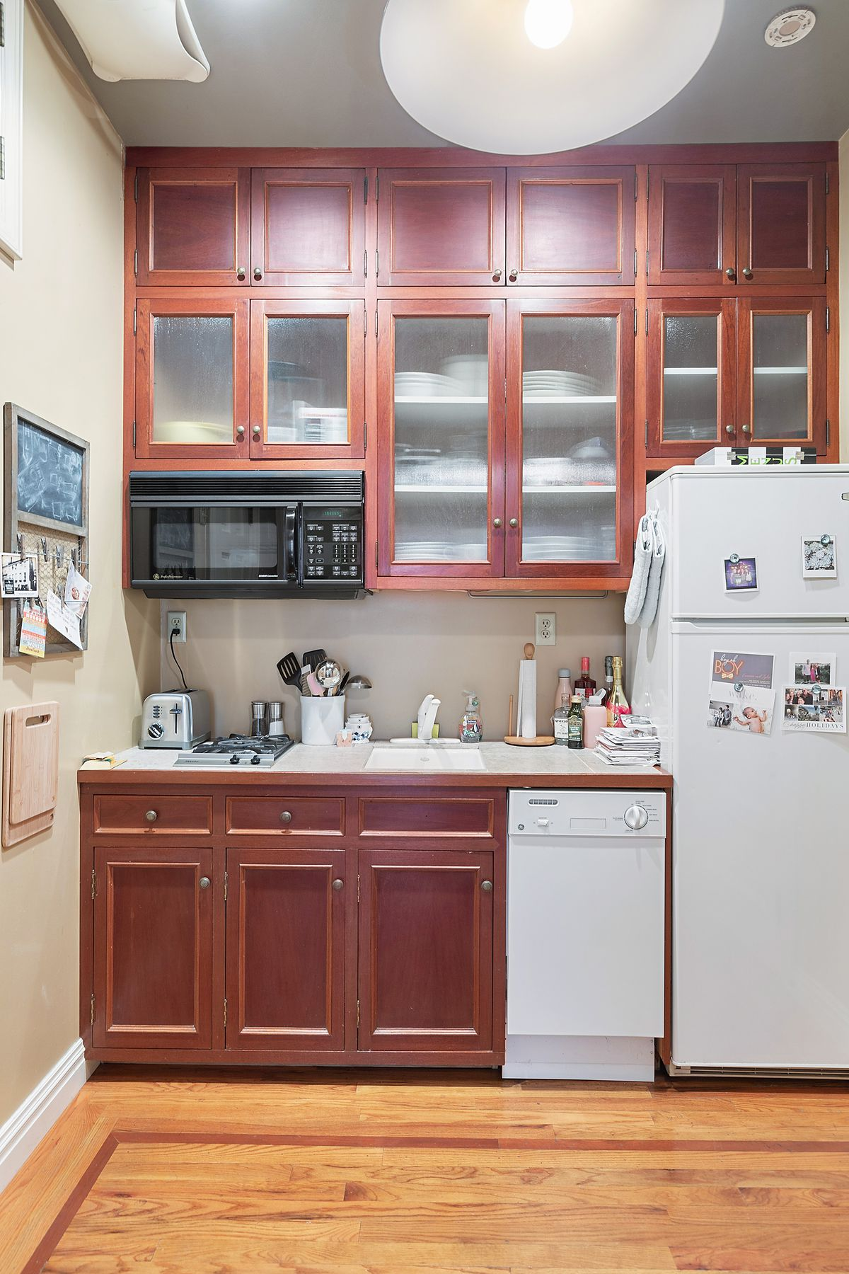 A kitchen with hardwood floors and wood cabinetry.