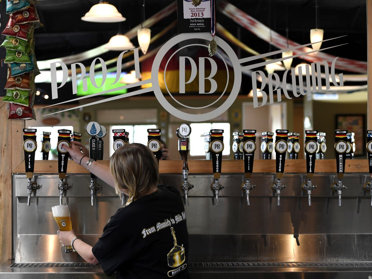 A photo of a bartender with her back turned to fill up a mug of beer from one of several visible taps at Prost Brewing Co. & Biergarten