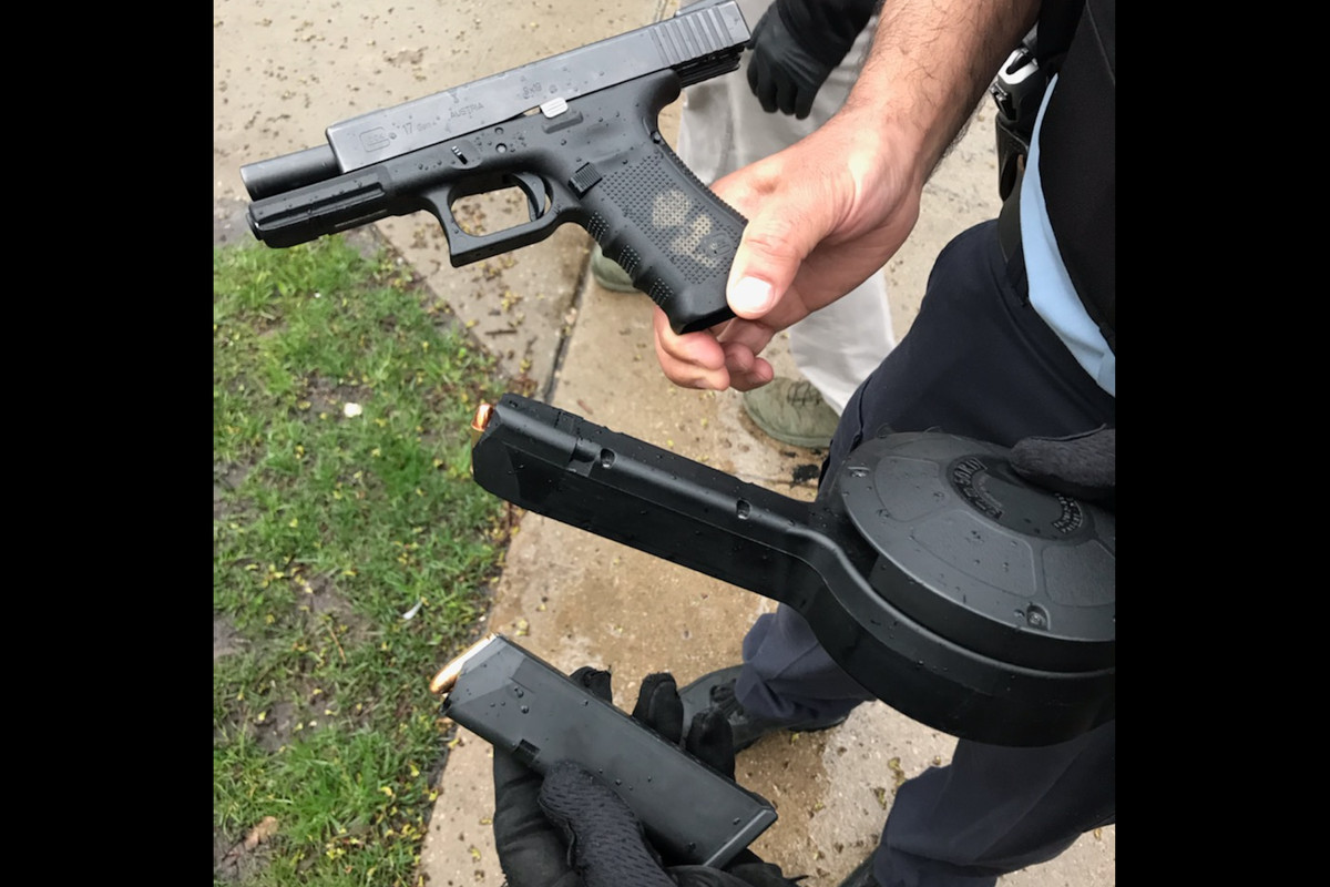 Police hold a weapon allegedly recovered during the arrest of a man charged with shooting at people in Beach Park on March 1, 2020.