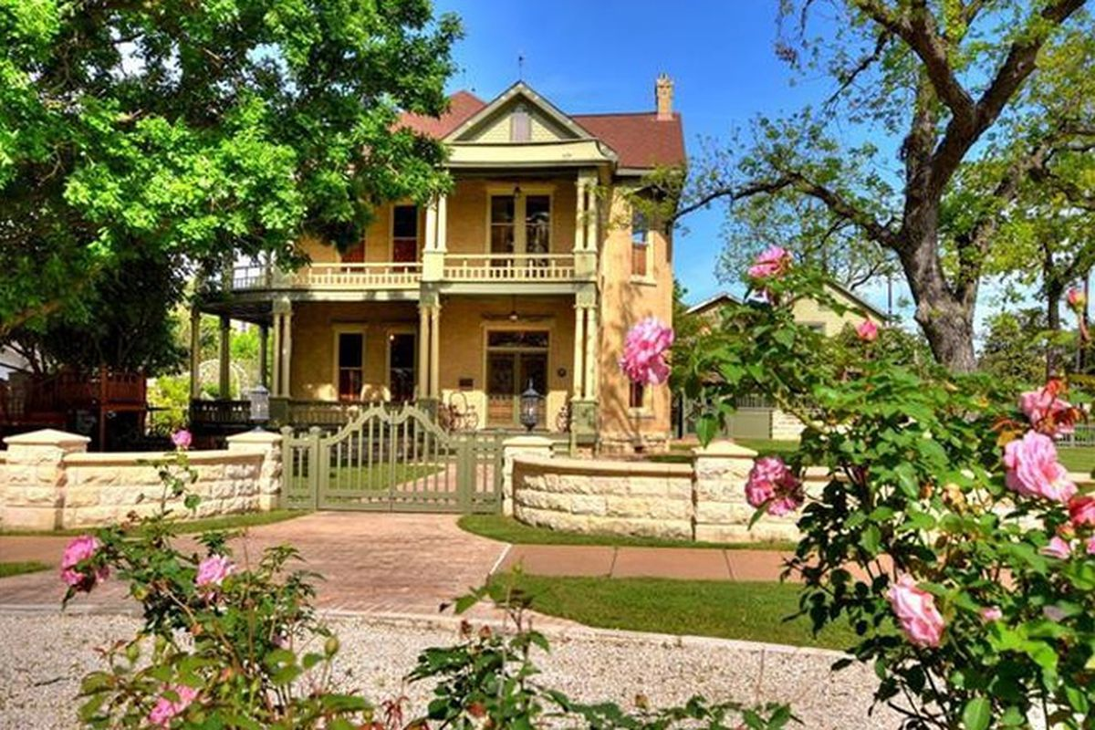 Two story historic home with huge front porch and second-story veranda, sort of Victorian