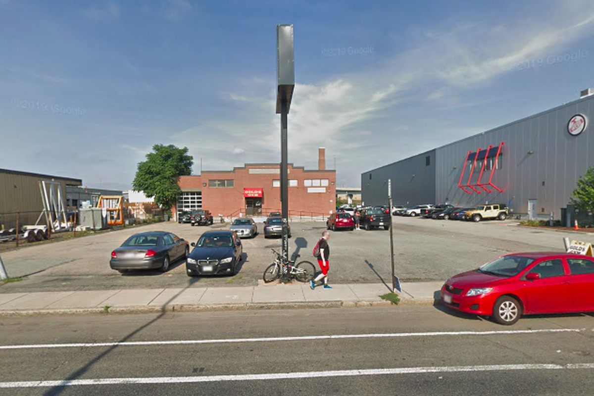 A largely vacant parking lot along a busy sidewalk with a squat building in the background.