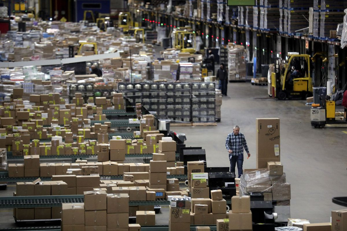 Employees work at the Associated Foods Stores distribution warehouse in Farr West, Weber County, on Tuesday, March 17, 2020.