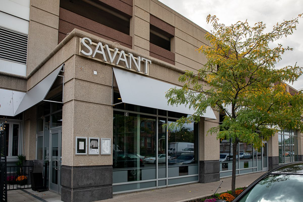 The exterior of Savant has a silver sign and matching silver awnings on a tan colored building.
