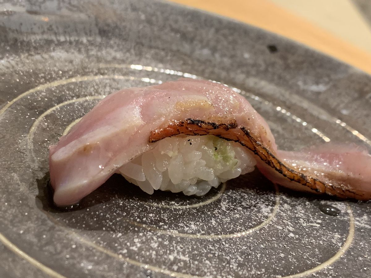 A piece of nigiri sushi on a place at Soichi.