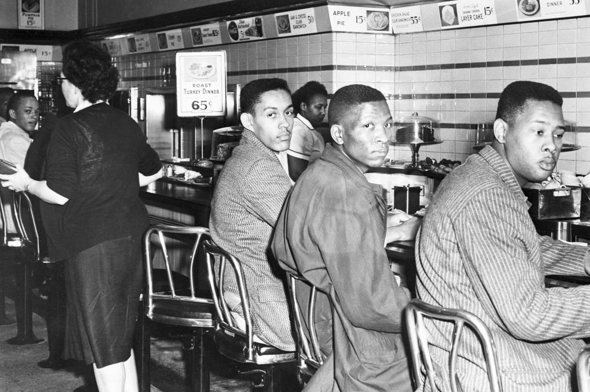 Three black college students participate in a lunch counter sit-in at a Woolworth's department store in Greensboro, North Carolina.