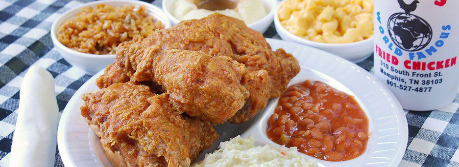 A plate of fried chicken with beans, coleslaw, mac and cheese, mashed potatoes, and rice.