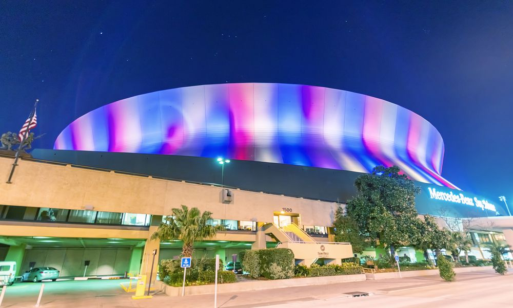 The exterior of the Mercedes Benz superdome in New Orleans. The building resembles a space craft and is domed. there are colorful lights illuminating the facade.