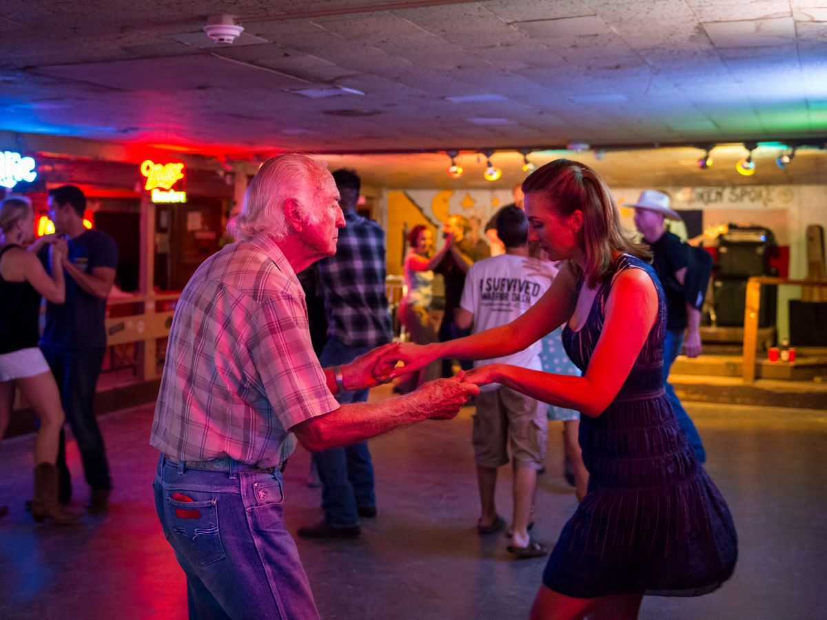 An elderly white man and a young white woman dancing on a wooden dance floor with other people dancing in background.