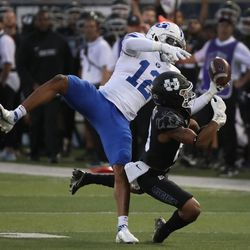 Brigham Young Cougars defensive back Malik Moore (12) intercepts against Utah State Aggies wide receiver Deven Thompkins (13) in Logan on Friday, Oct. 1, 2021.