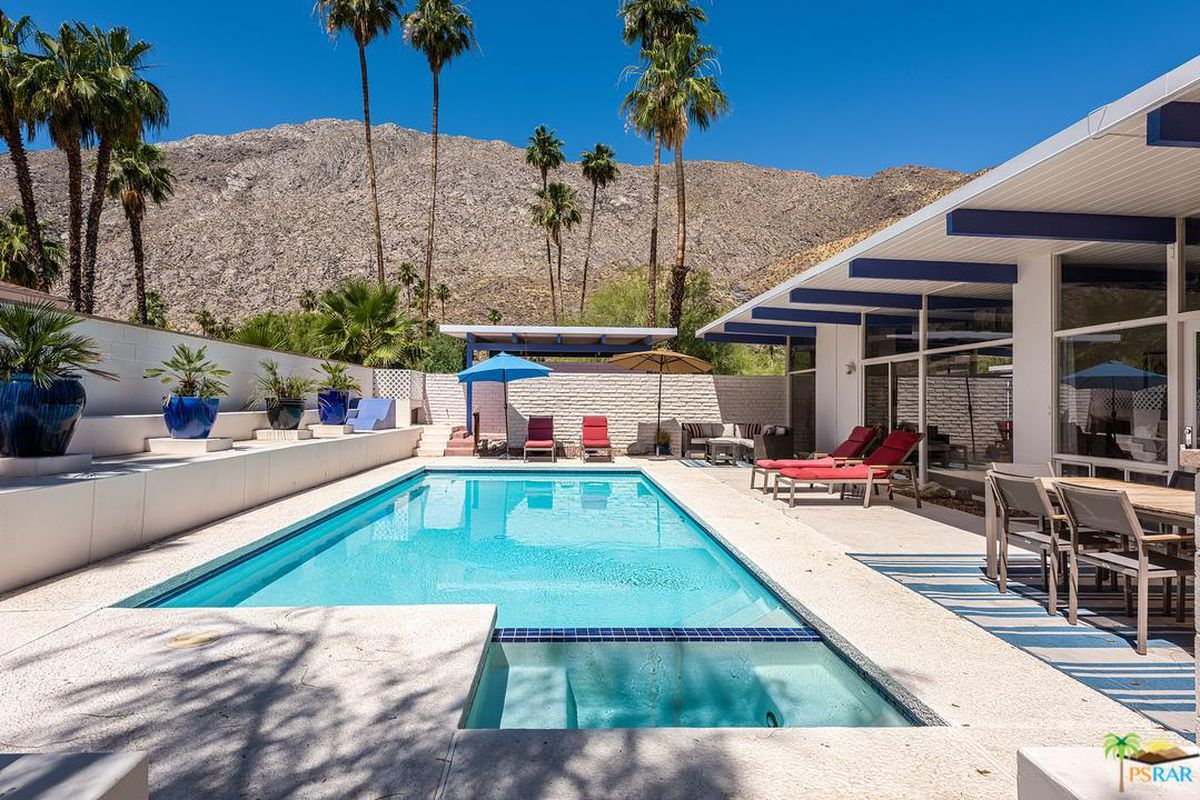 Shot of backyard with pool and overhanging roof with blue-painted beams.