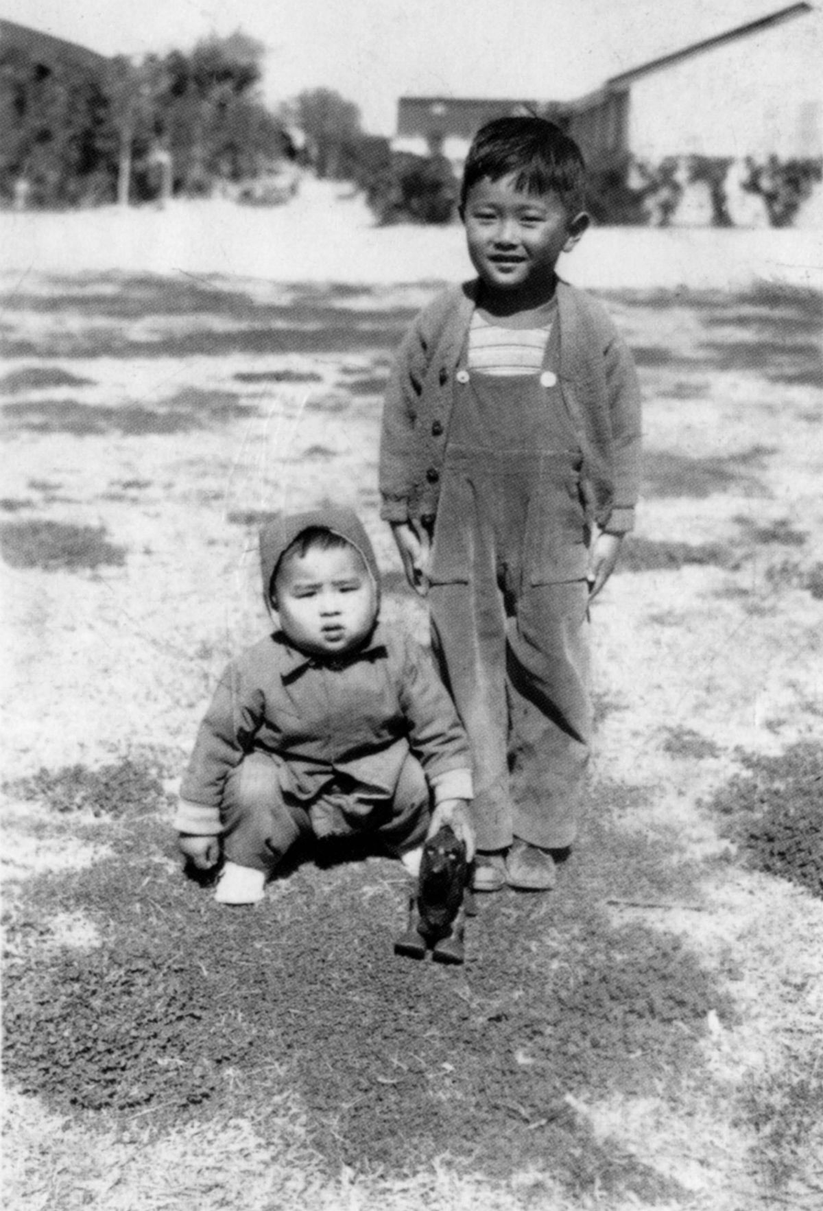 """Sun-Times editor Frank Sugano (seated, with toy) and his brother Bill at the Gila River internment camp in Arizona where Frank was born. He became a respected Sun-Times editor. 