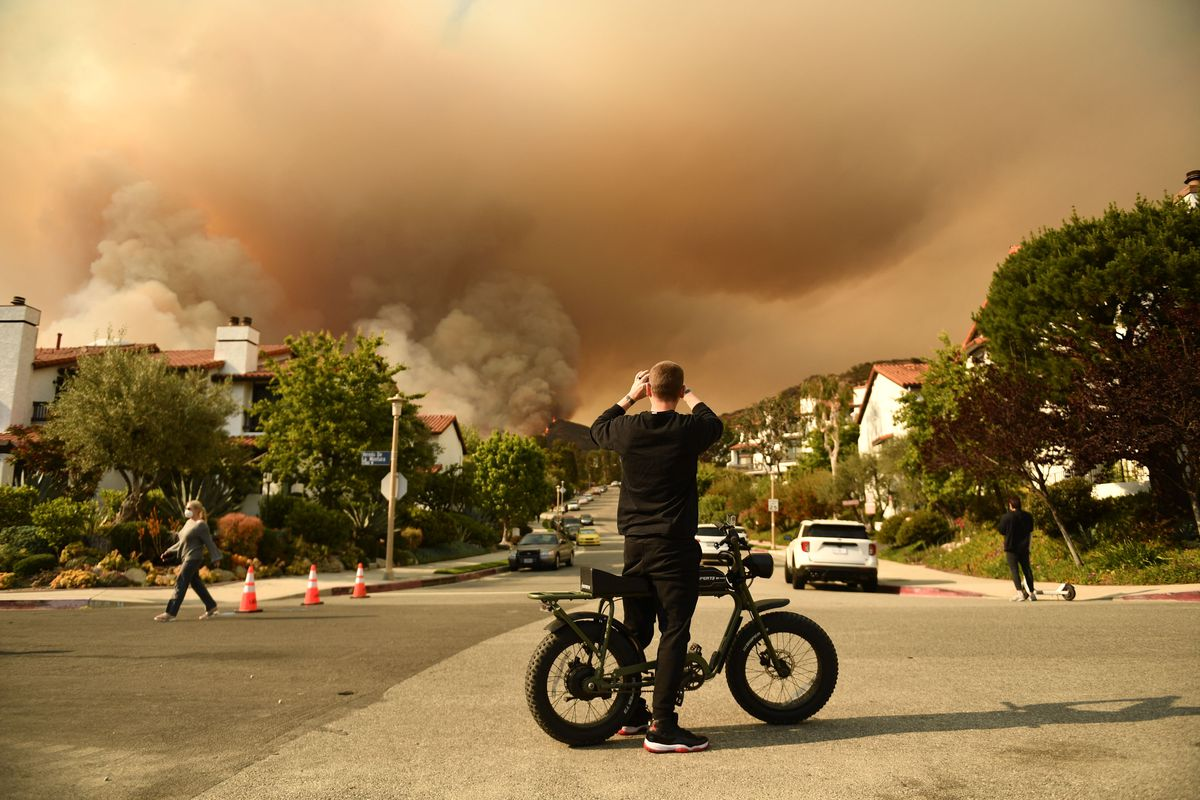 A man standing beside his bike in a suburban intersection takes a photo of the plume of smoke created by the Palisades fire in Topanga State Park.