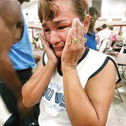Isabell Oliver of New Orleans cries while waiting with her family to register for assistance as refugees from Hurricane Katrina at Convention Hall in Gadsden, Ala., Thursday. Oliver traveled with 12 people to Gadsden to escape Hurricane Katrina and still has not heard from two of her four daughters that evacuated elsewhere.