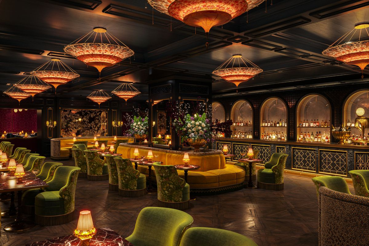 An ornate, low-lit bar and restaurant bedecked in gold trim, chandeliers, and dark wood finishing