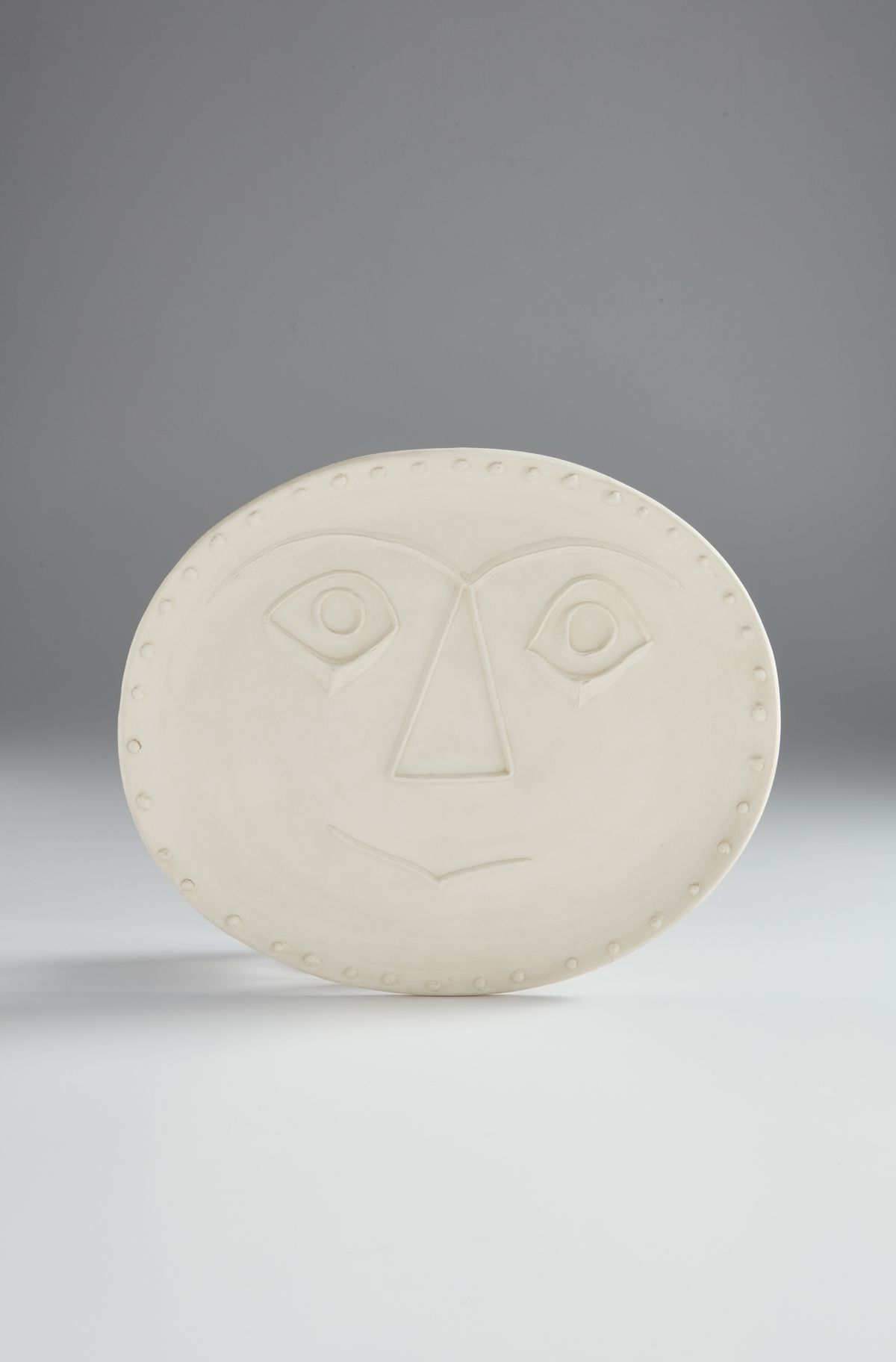 A white tablet with a face carved into it.