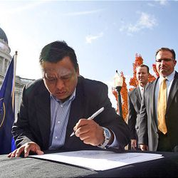 Tony Yapias of Proyecto Latino signs a document called the Utah Compact in support of immigration reform at the State Capitol in Salt Lake City Thursday.