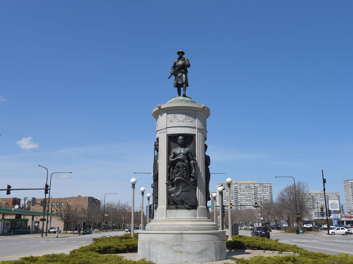 A monument in with a solider with a musket in its hand.
