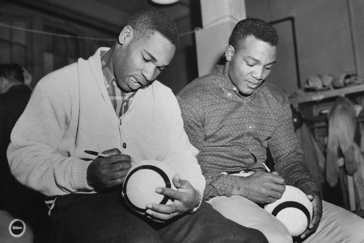 Jim Brown and Bobby Mitchell Signing Footballs