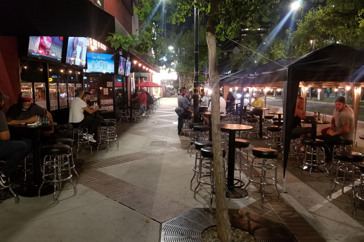 A sidewalk sports bar with outdoor TVs for watching games, and tall tables to sit.