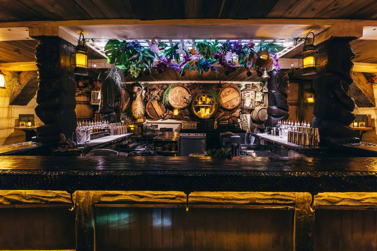 The bar at Undertow, with plants hanging from the ceiling and barrel designs in the background