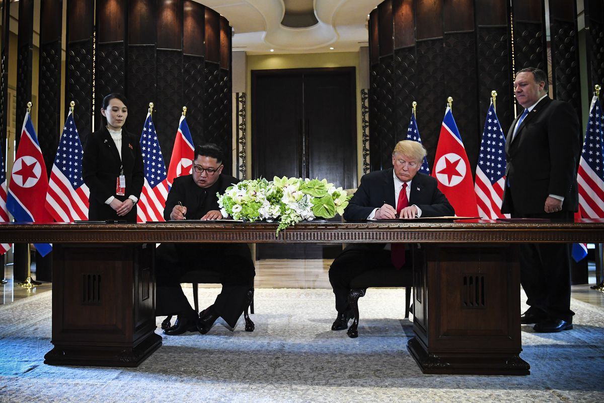 President Donald Trump and Kim Jong Un sign documents as US Secretary of State Mike Pompeo (R) and the North Korean leader's sister Kim Yo Jong (L) look on at a signing ceremony during their historic US-North Korea summit, at the Capella Hotel on Sentosa