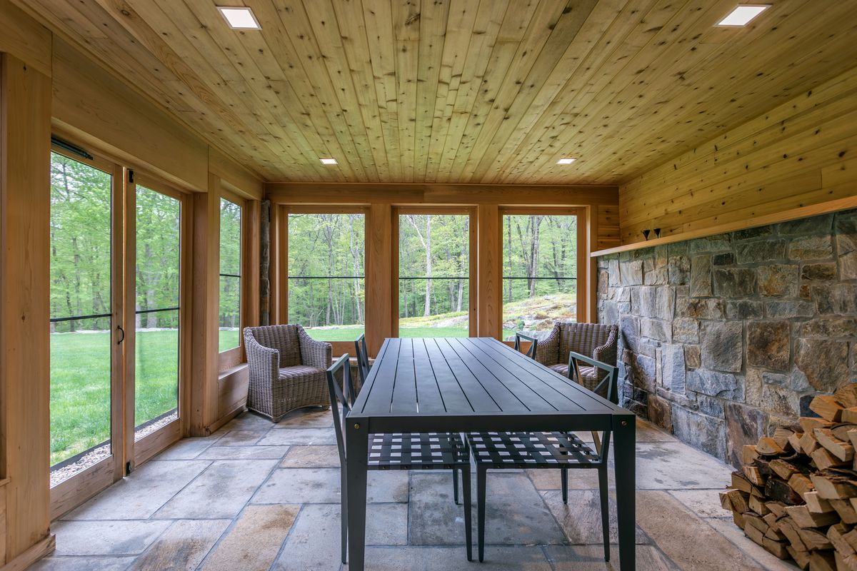 An enclosed patio has a large table, two chairs, stone walls, and a firewood pile.