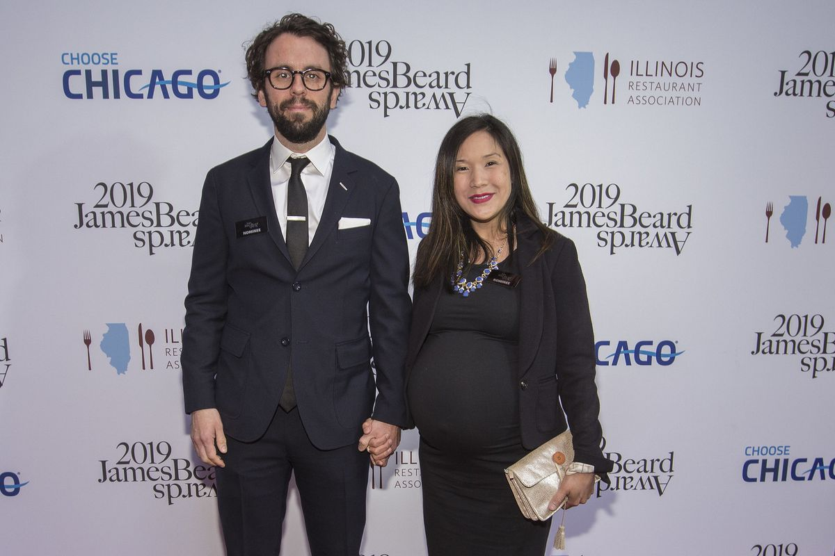 Johnny Clark and a pregnant Beverly Kim stand together holding hands and smiling.