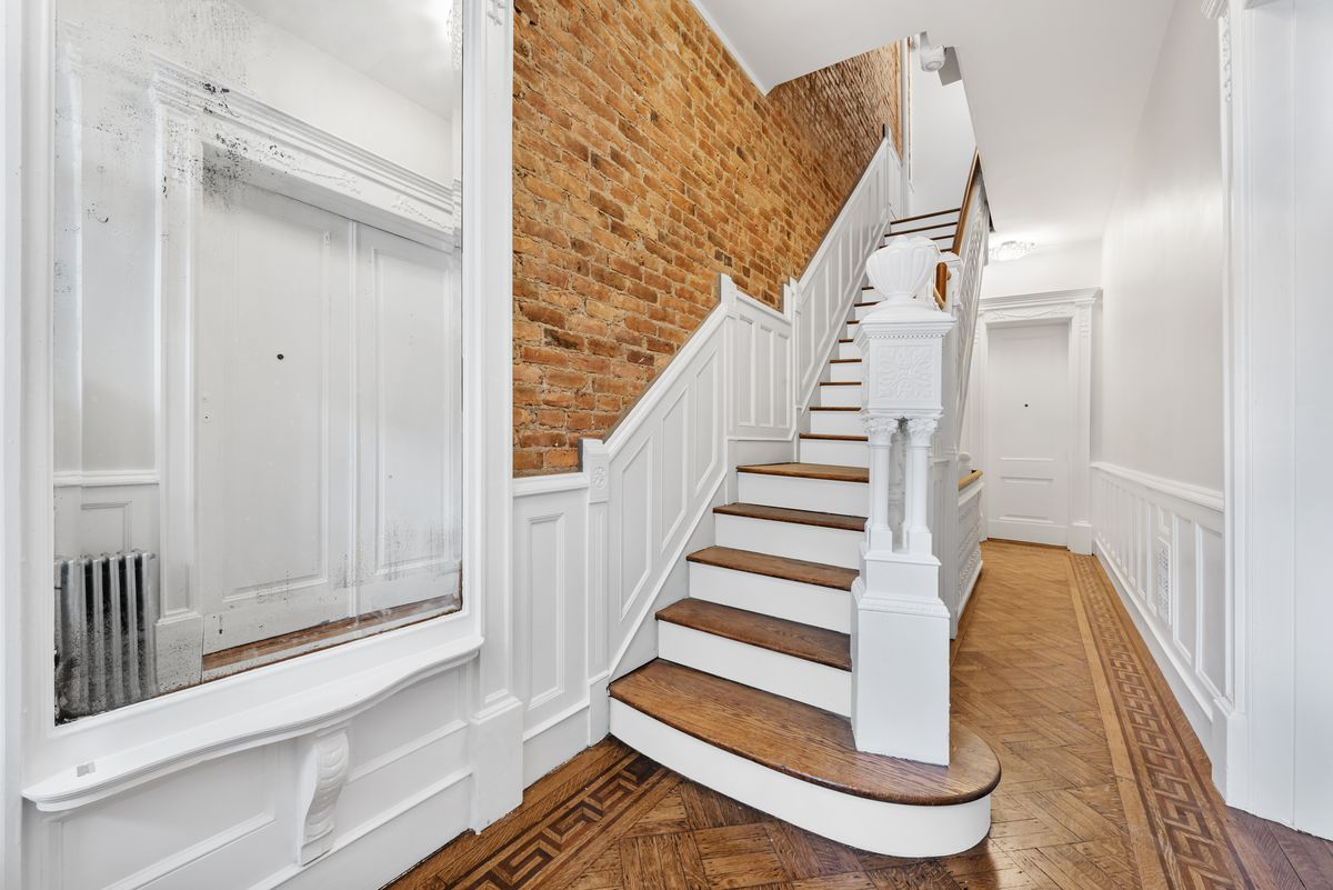An entrance with parquet floors, exposed brick, and a white and wooden staircase.