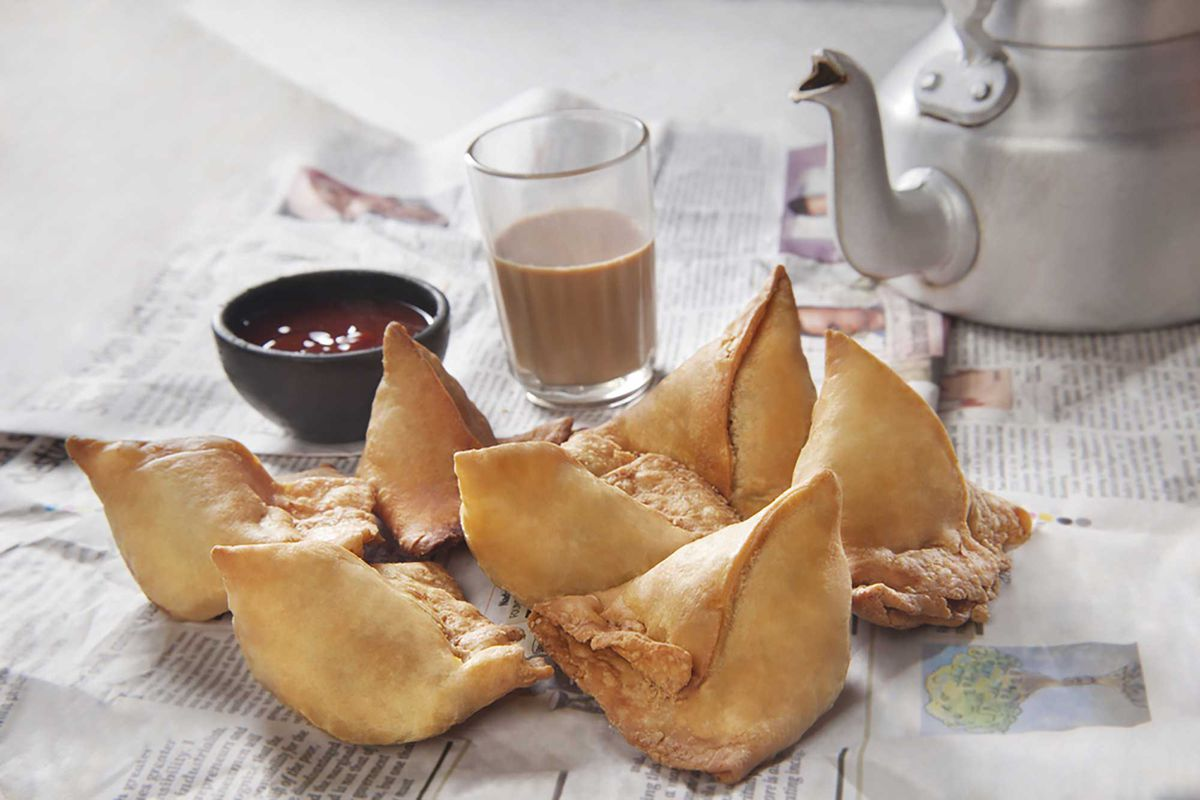 Seven samosas on a newspaper with a pot of tea in the background