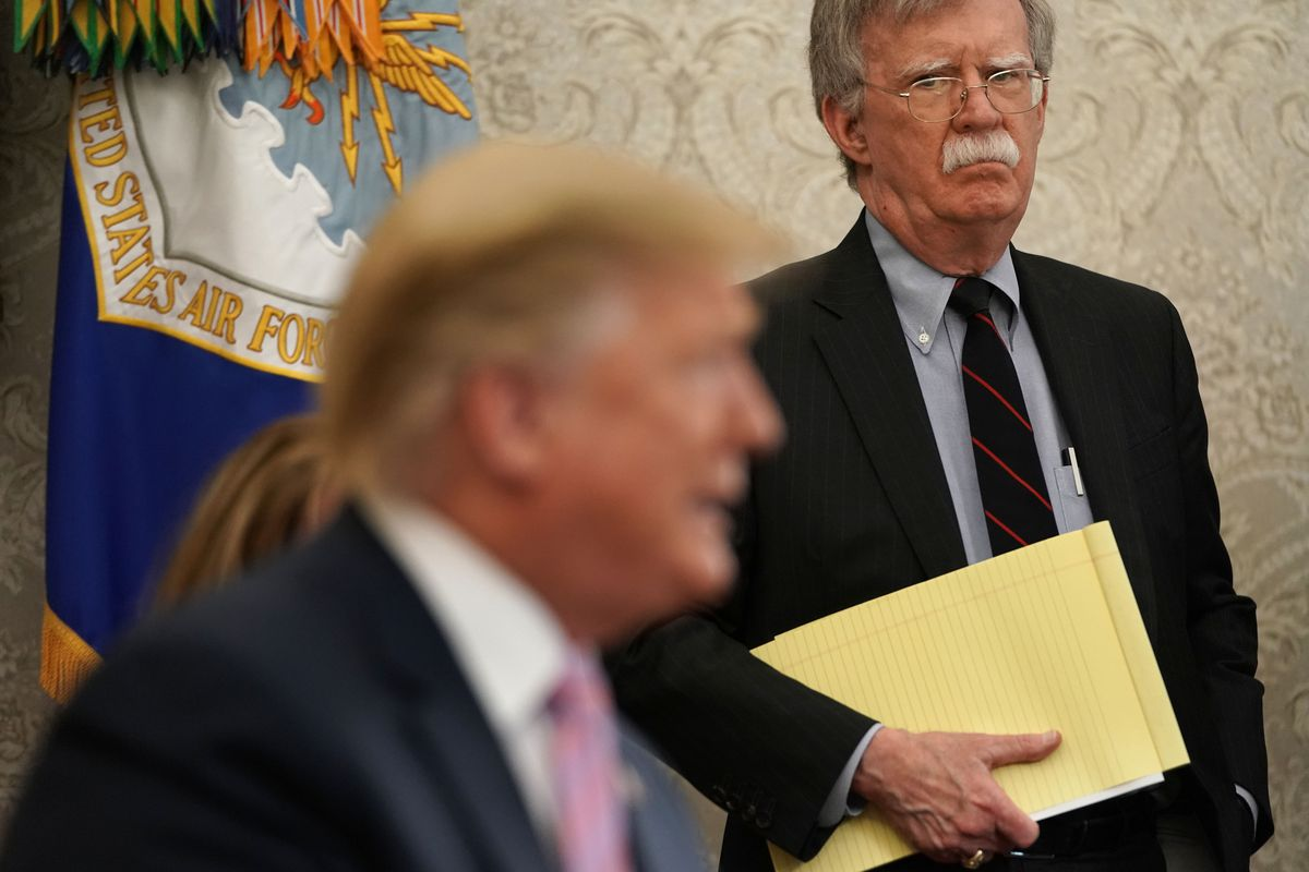 Bolton behind Trump holding a yellow notepad.