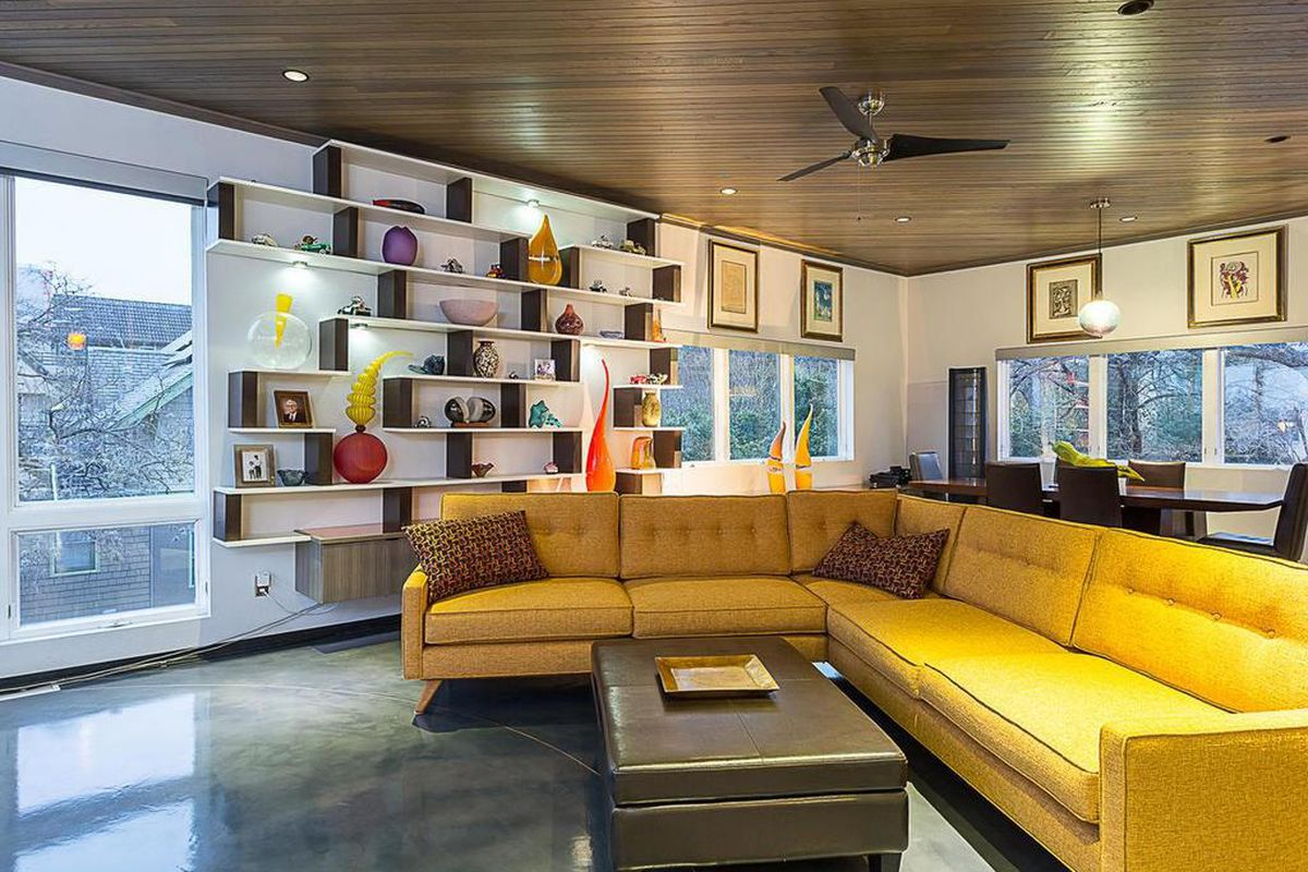 Condo living room with white walls, support beams, yellow couch, views