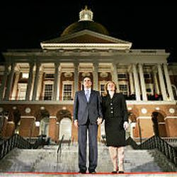 Outgoing Gov. Mitt Romney and Ann Romney listen to a 19-gun salute during his final walk out of the Statehouse in Boston on Jan. 3, 2007. Romney slashed spending during his tenure as governor.