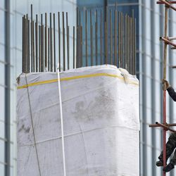 A worker climbs on scaffolding at a road construction site in Beijing Thursday, April 12, 2012. China's economic growth fell to its lowest level in nearly three years in the first quarter of 2012 amid weak trade and lending controls.