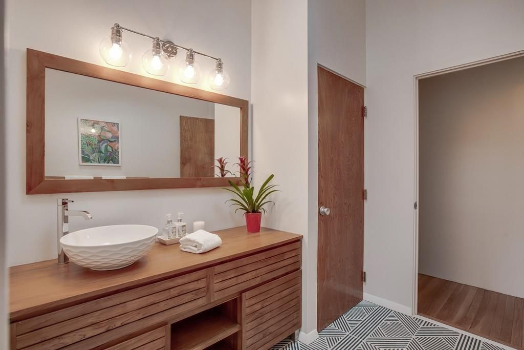 A bathroom with a long vanity and a basin sink.