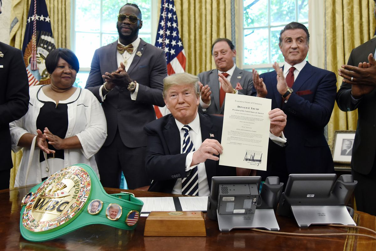 President Donald Trump holds his signed clemency grant for boxer Jack Johnson. Attending the signing (from left) were Johnson's great-great niece Linda Haywood, Deontay Wilder, Keith Frankel, Sylvester Stallone and Lennox Lewis. | Getty Images