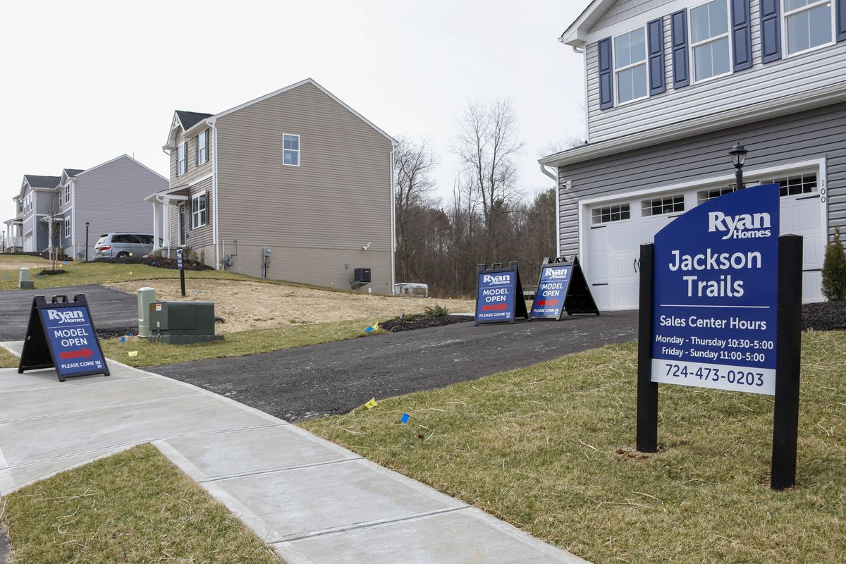 Model homes and for sale signs line the streets as construction continues at a housing plan in Zelienople, Pa., Wednesday, March 18, 2020.